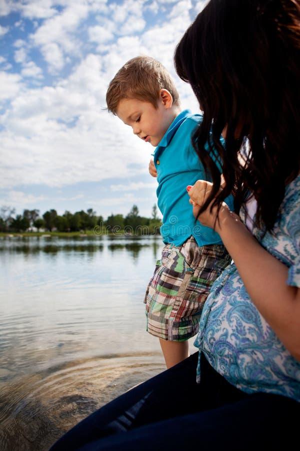 Мать играя в воде с сыном стоковое фото