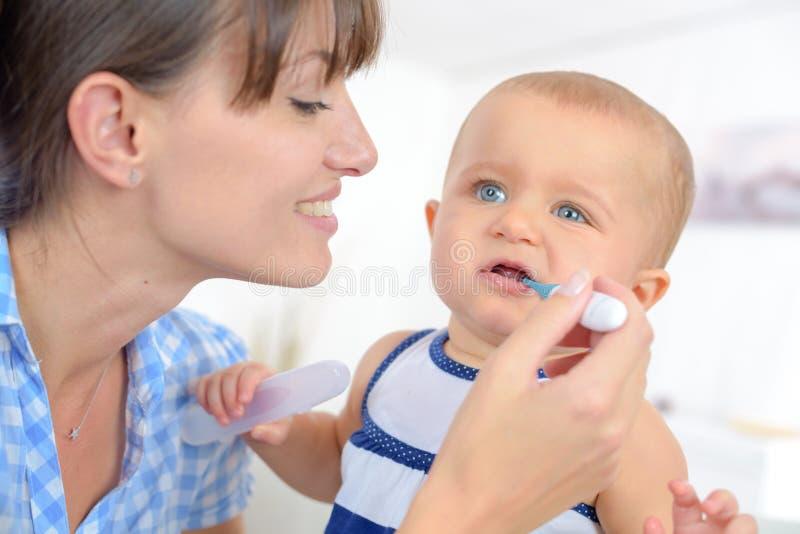 Мать измеряет ребенка младенца температуры стоковые фотографии rf