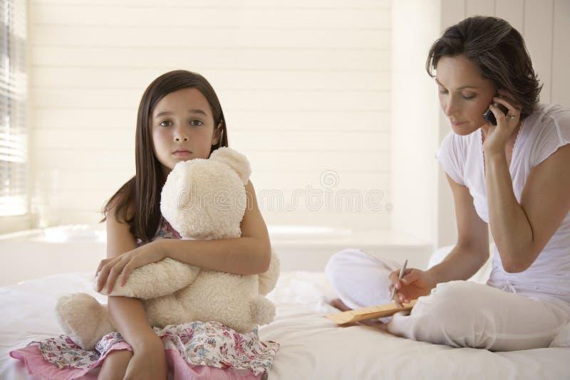 Мать используя мобильный телефон при дочь держа игрушечного сидя на кровати стоковое изображение rf