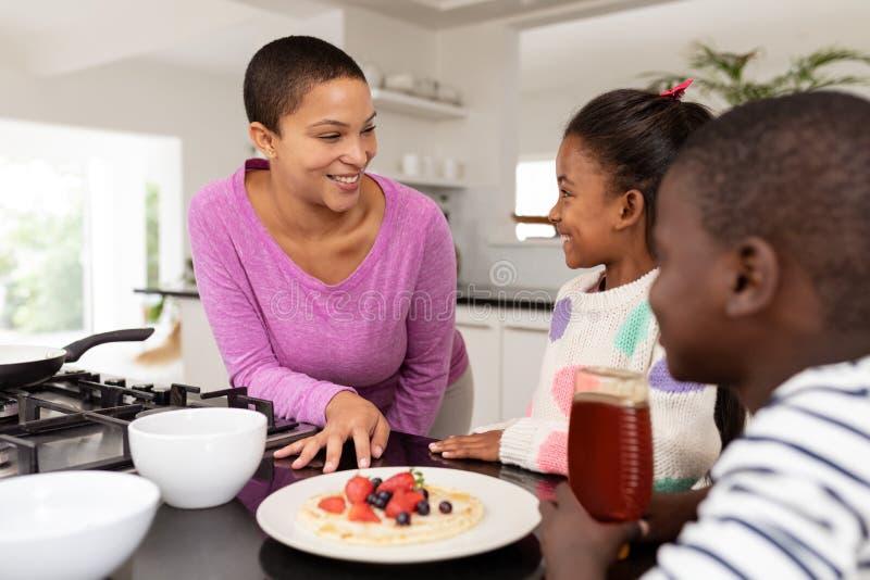Мать и дети подготавливая еду на worktop в кухне стоковые фотографии rf