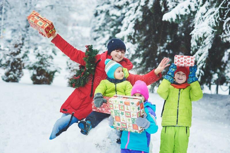 ????? ?????????? мать и 3 дет играя в лесе зимы стоковое фото
