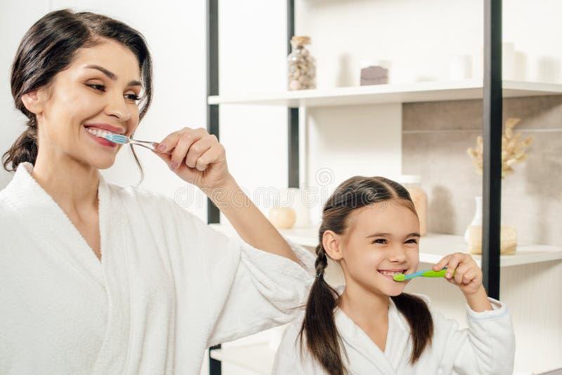 мать и дочь в белых купальных халатах чистя зубы щеткой с зубными щетками стоковая фотография