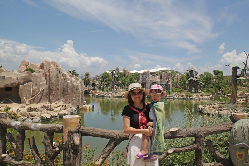 Мать и дочь в парке с зеленым озером , горным и голубым небом стоковое изображение