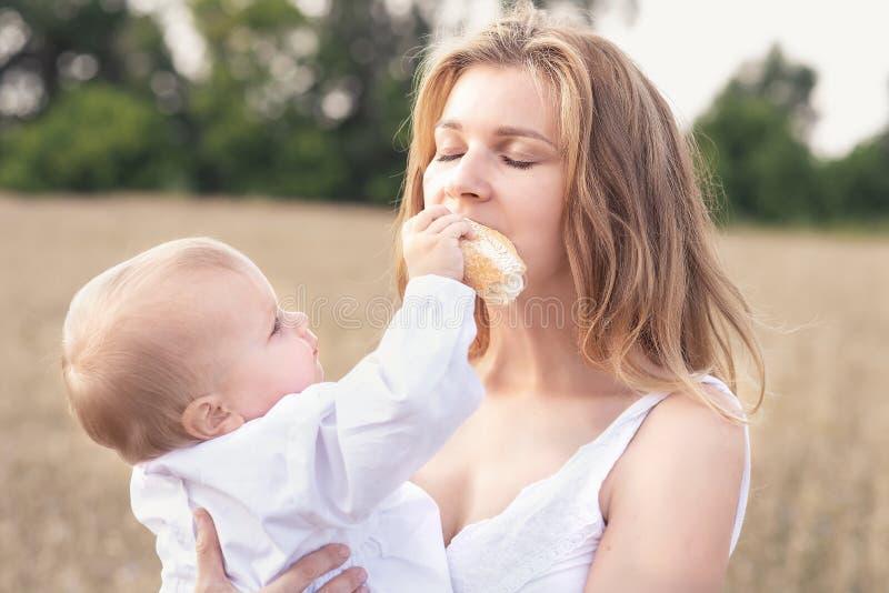 Мать и дочь в пшеничном поле семья счастливая outdoors здоровый ребенок с матерью на пикнике с хлебом и молоком в золотом стоковые фотографии rf