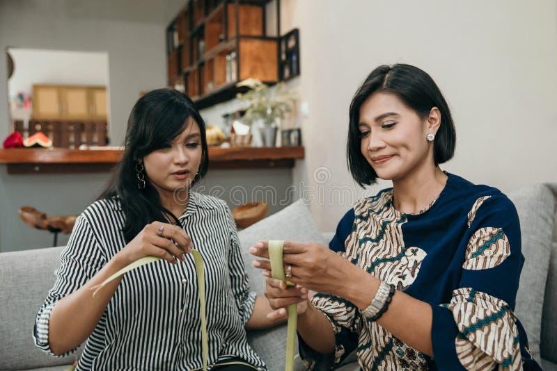 Мать и дочь делают сплетенную оболочку ketupat стоковое фото