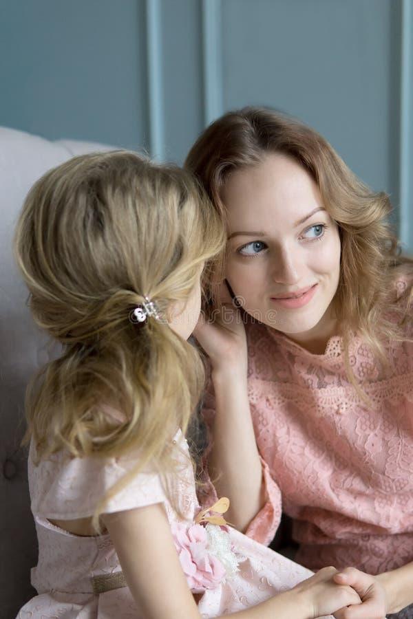 Мать и дочь деля секреты дома в живущей комнате стоковые изображения