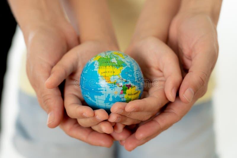 Мать и дочь держа глобус мира в концепции eduction и защиты стоковые изображения