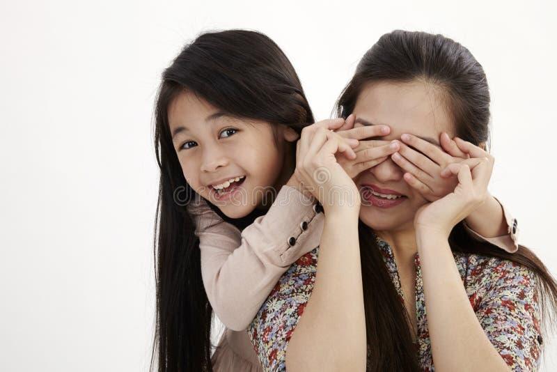 Мать и дочь играя взгляд украдкой шиканье стоковые фотографии rf