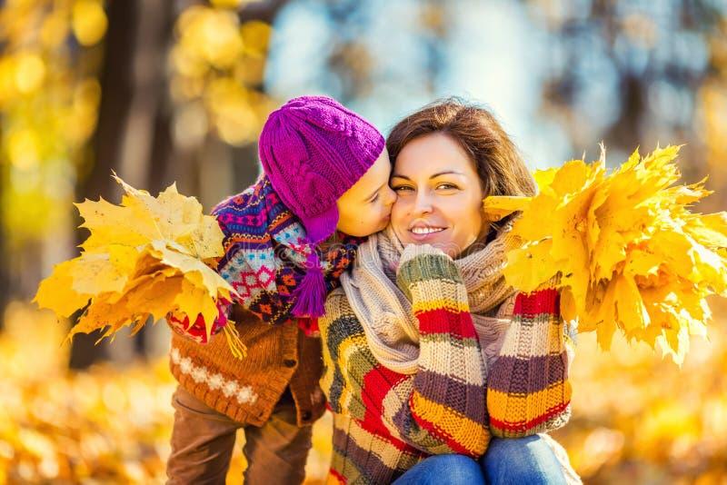 Мать и дочь играя в парке осени стоковые изображения