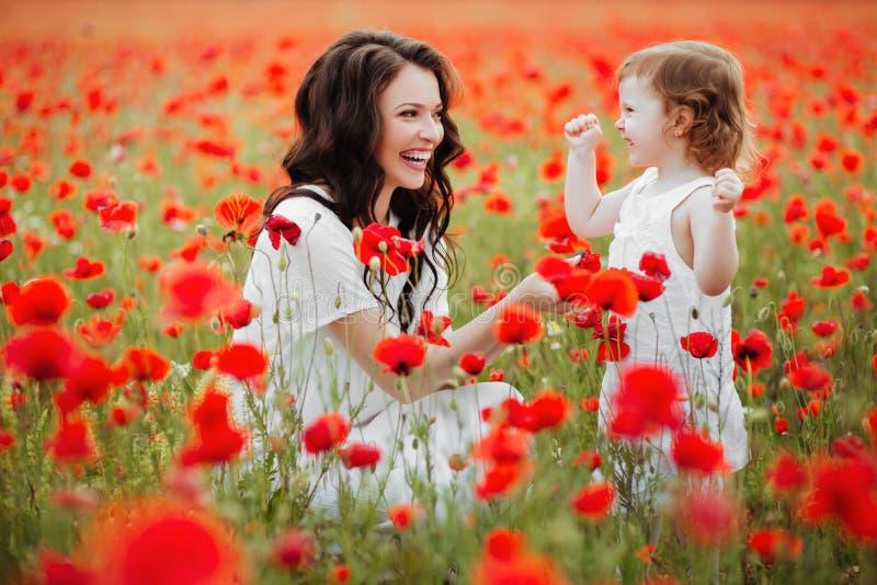 Мать и дочь играя в поле цветка стоковое изображение