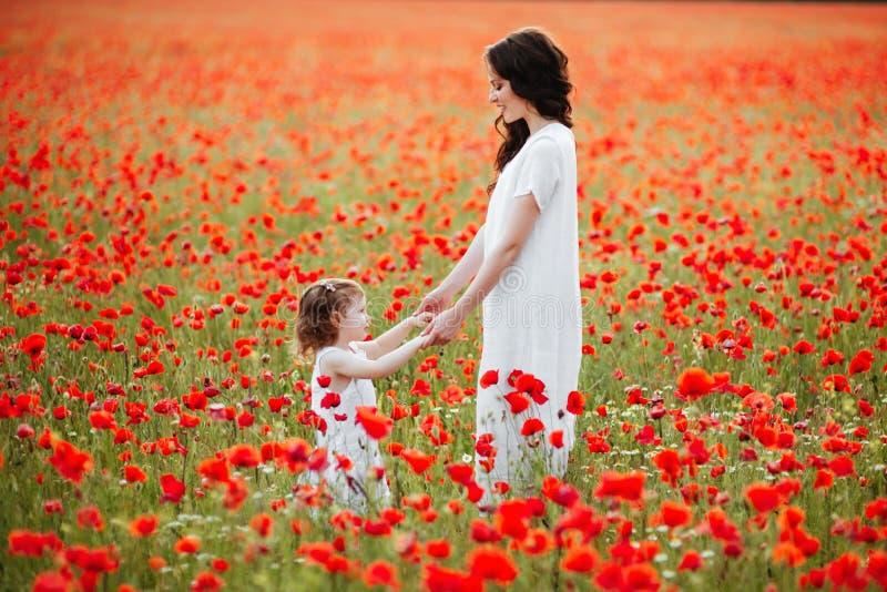 Мать и дочь играя в поле цветка стоковая фотография