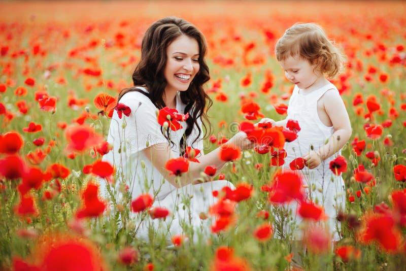 Мать и дочь играя в поле цветка стоковое фото