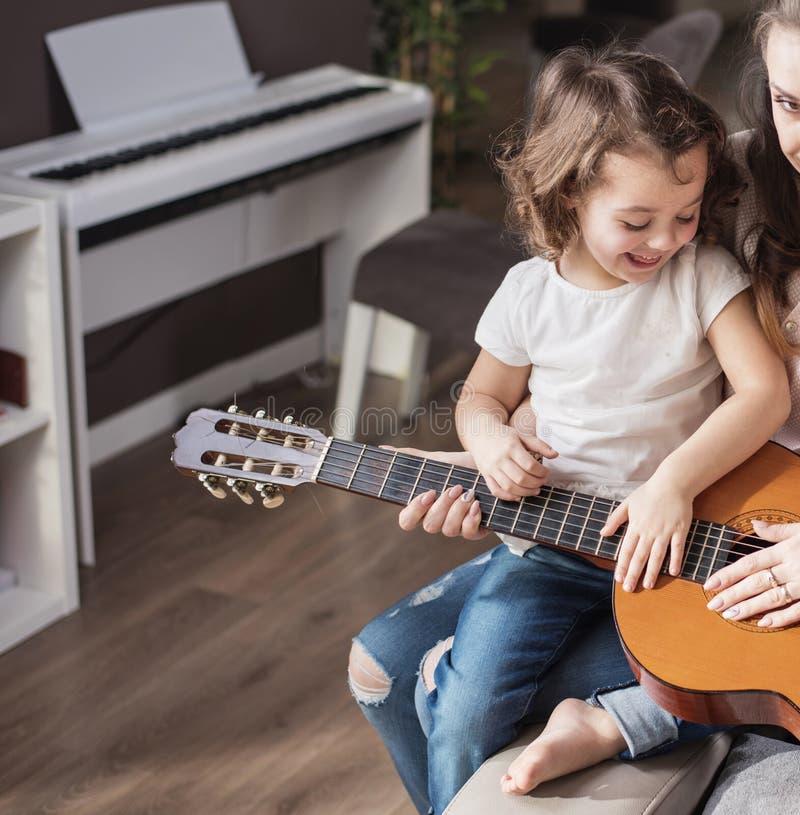 Мать и дочь играя гитару стоковые фото