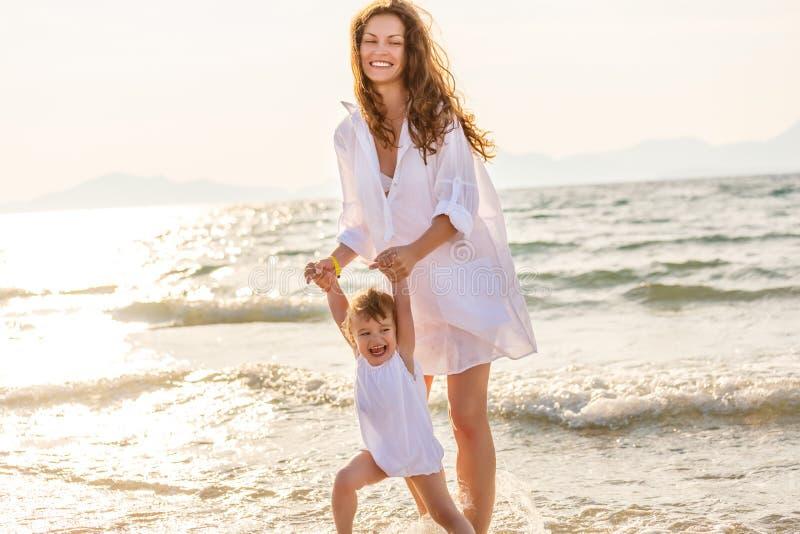 Мать и дочь играя на пляже моря в Греции стоковая фотография rf