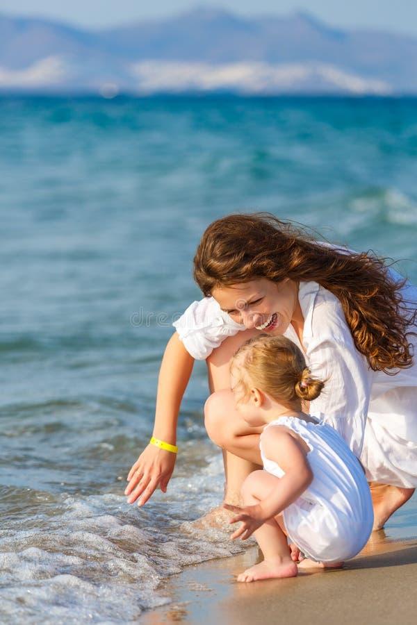 Мать и дочь играя на пляже стоковая фотография