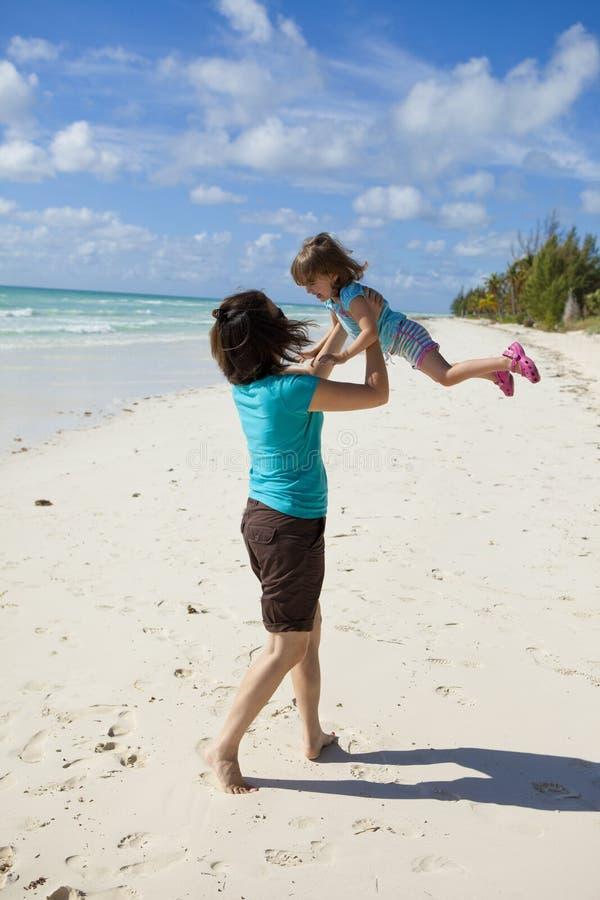 Мать и дочь играя океаном стоковые изображения