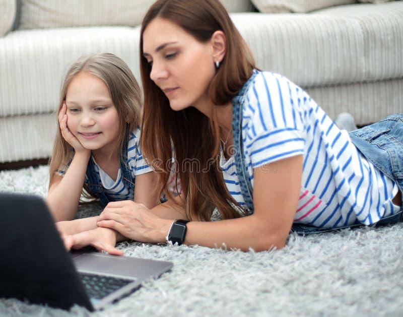 Мать и дочь используя ноутбук в их доме стоковые фотографии rf