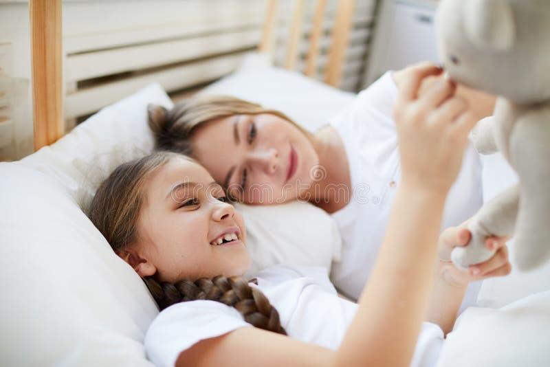 Мать и дочь лежа в кровати стоковые изображения rf