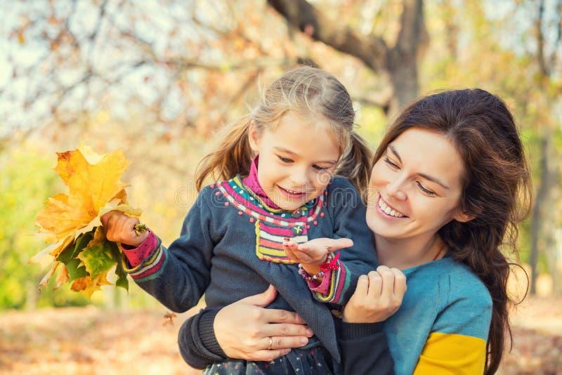 Мать и дочь наслаждаются солнечной осенью в парке стоковое изображение rf
