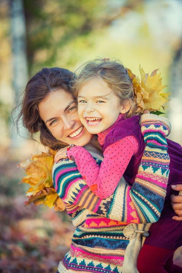 Мать и дочь наслаждаются солнечной осенью в парке стоковое фото