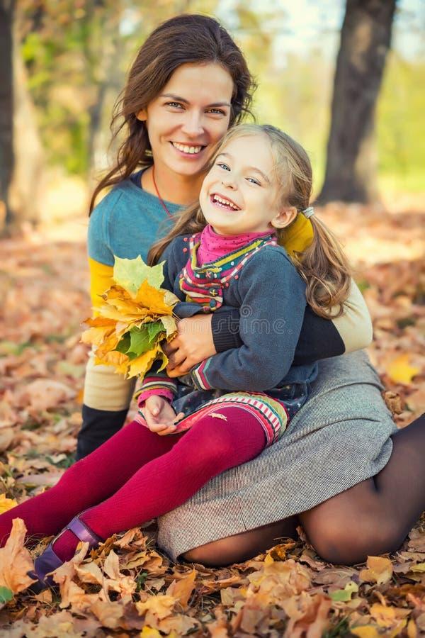 Мать и дочь наслаждаются солнечной осенью в парке стоковые фото