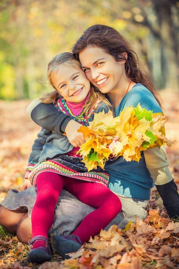 Мать и дочь наслаждаются солнечной осенью в парке стоковое изображение
