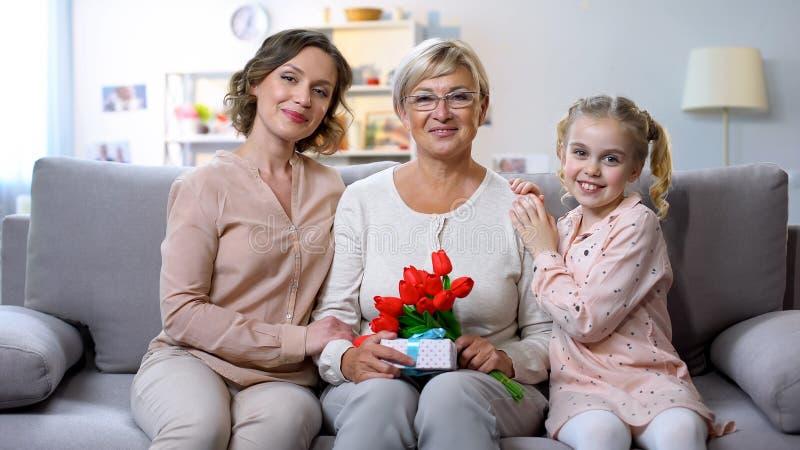 Мать и дочь обнимая бабушку с тюльпанами и настоящий момент в руке, празднике стоковое фото rf