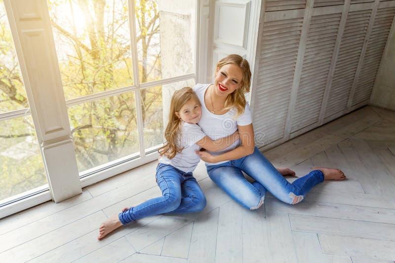 Мать и дочь обнимая около windiow стоковое изображение