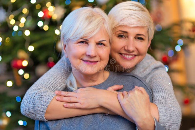 Мать и дочь обнимая рождественской елкой стоковое фото rf