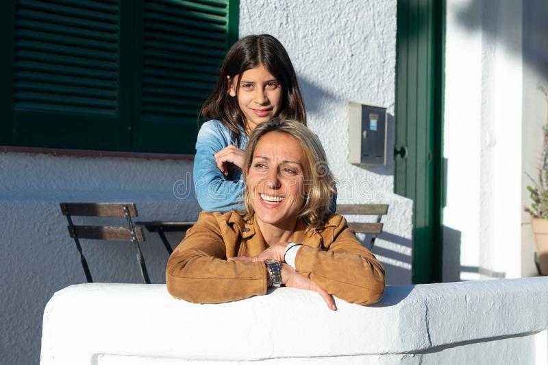 Мать и дочь обняли в заходе солнца в среднеземноморской деревне с белыми стенами стоковое фото