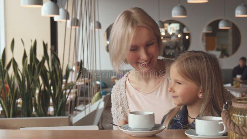 Мать и дочь показывают их большие пальцы руки вверх на кафе стоковые фотографии rf