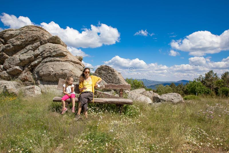 Мать и дочь сидя на деревянной скамье в сельской местности Мадрида стоковые фотографии rf