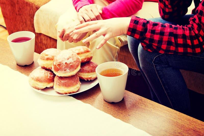 Мать и дочь сидя на кресле с donuts и чае на таблице стоковые фотографии rf