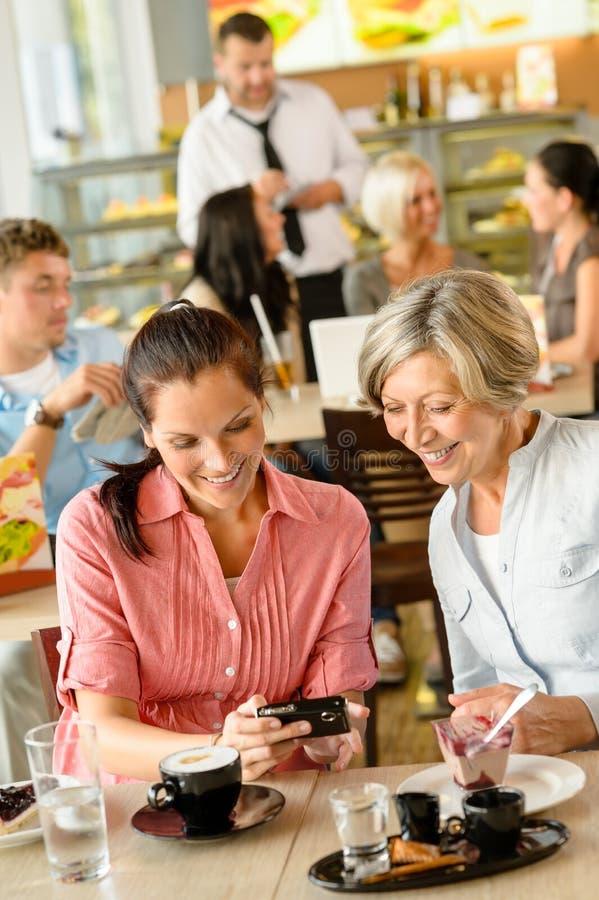 Мать и дочь смотря кафе изображений стоковое фото rf