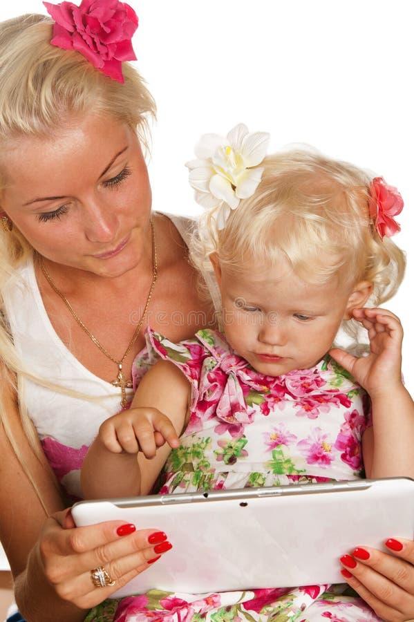 Мать и дочь смотря таблетку стоковое фото