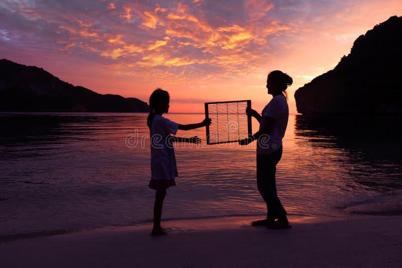 Мать и дочь стоя на пляже с красным заходом солнца неба стоковые изображения rf