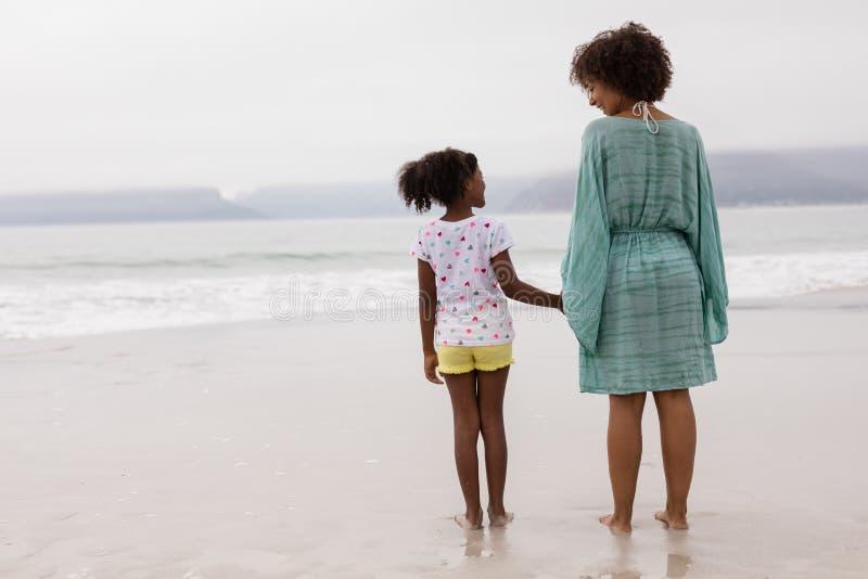 Мать и дочь стоя совместно на пляже стоковое изображение rf