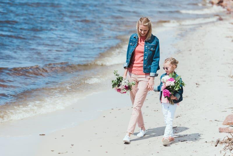 мать и дочь с флористическими букетами держа руки стоковое изображение rf