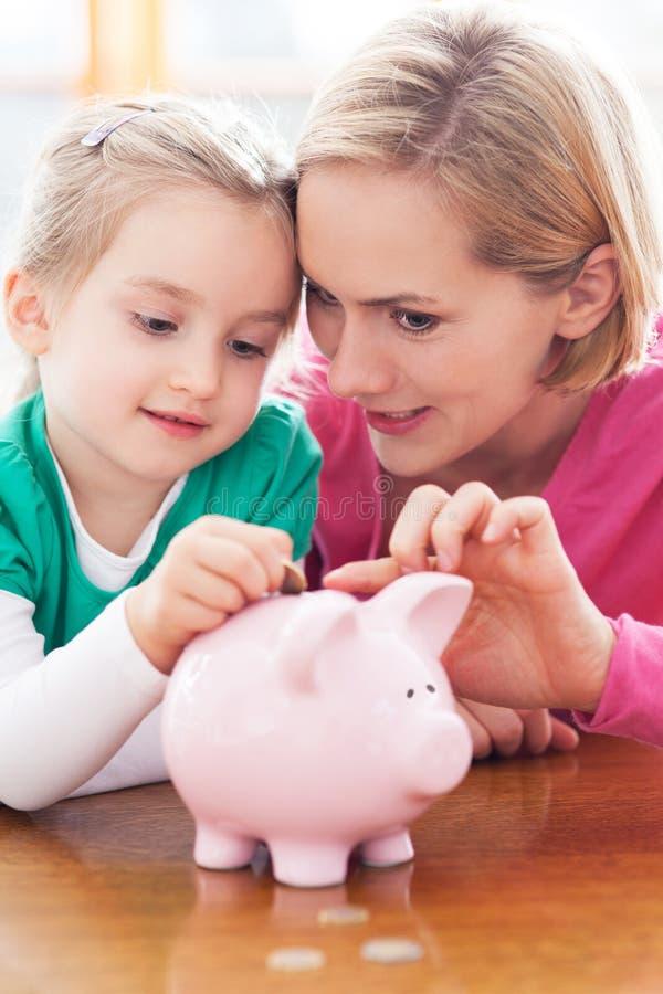 Мать и дочь с piggy банком стоковые изображения rf