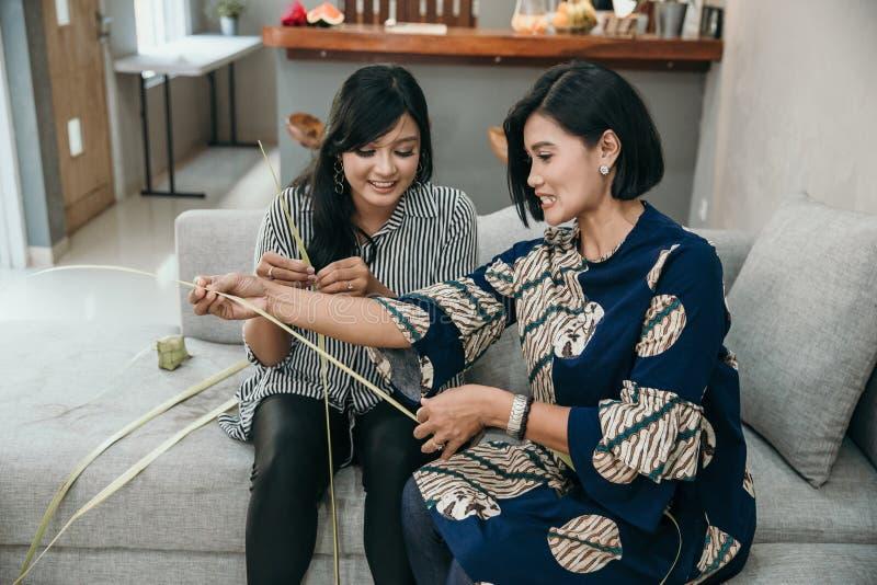 Мать и дочь уча как сделать сплетенную оболочку ketupat стоковые изображения rf
