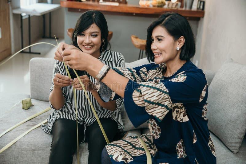 Мать и дочь уча как сделать сплетенную оболочку ketupat стоковое фото rf