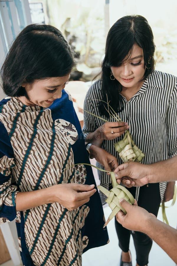 Мать и дочь уча как сделать сплетенную оболочку ketupat стоковая фотография