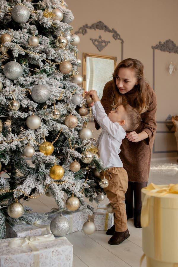 Мать и его маленький сын украшая рождественскую елку с игрушками и гирляндами стоковое изображение rf