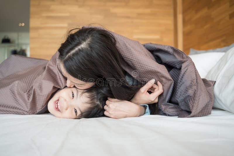 Мать и ее девушка ребенка дочери играя в спальне и кладя одеяло дальше Счастливая азиатская семья стоковое фото