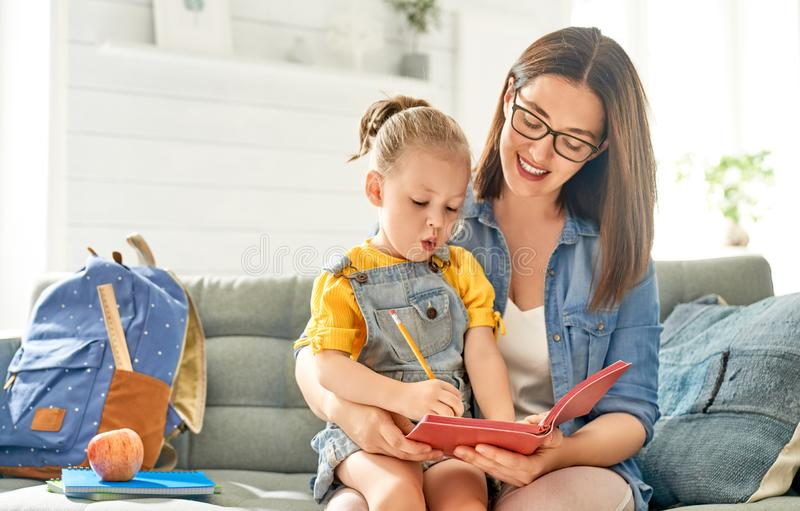 Мать и ее дочь пишут в тетради стоковое фото