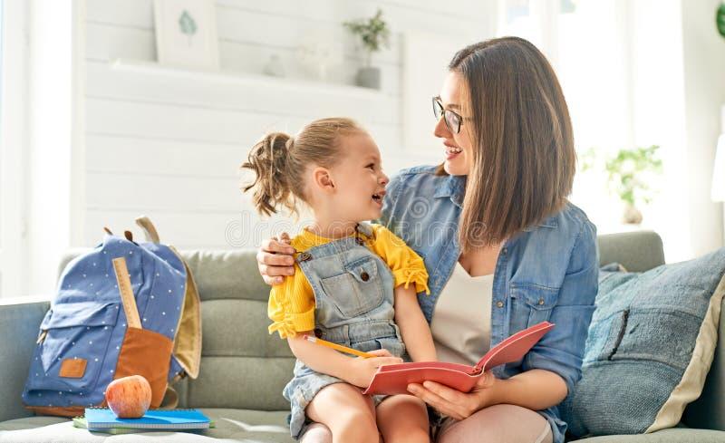 Мать и ее дочь пишут в тетради стоковая фотография