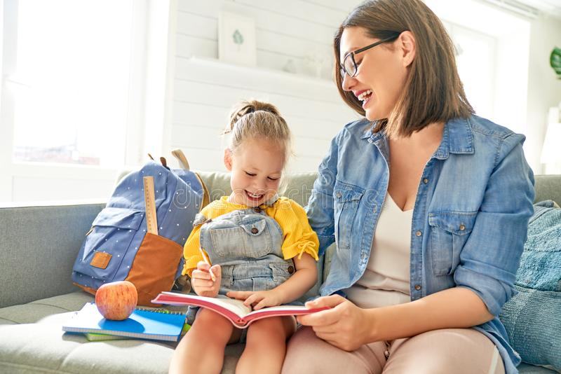 Мать и ее дочь пишут в тетради стоковое изображение rf