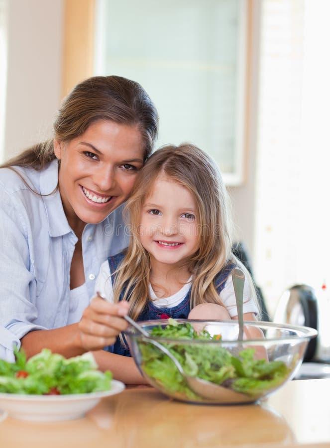 Мать и ее дочь подготовляя салат стоковое изображение rf