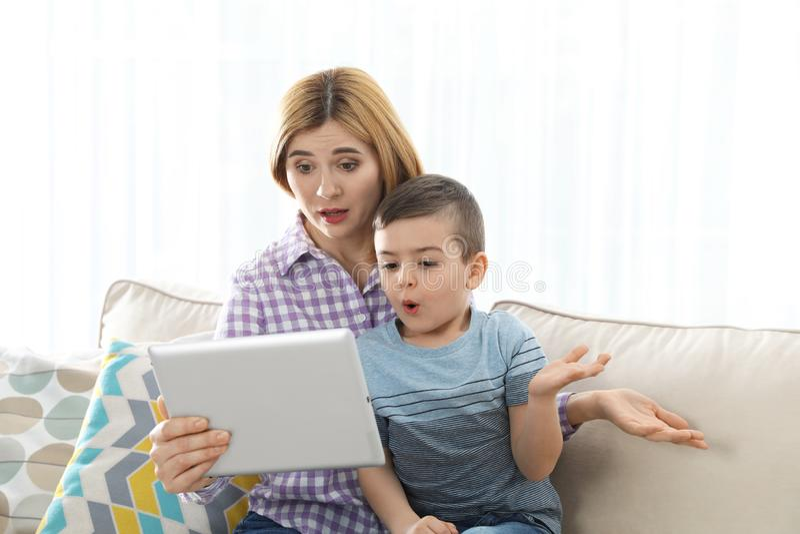 Мать и ее сын используя видео-чат на планшете стоковое фото rf