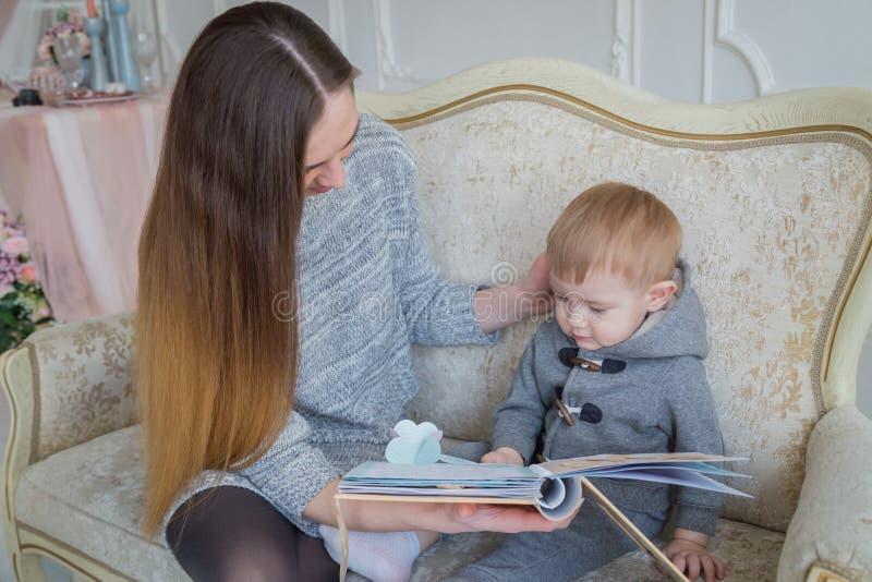 Мать и ее сын младенца смотря photobook стоковая фотография rf